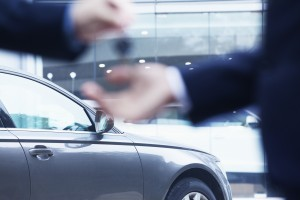 Salesman handing over keys for new car to young businessman